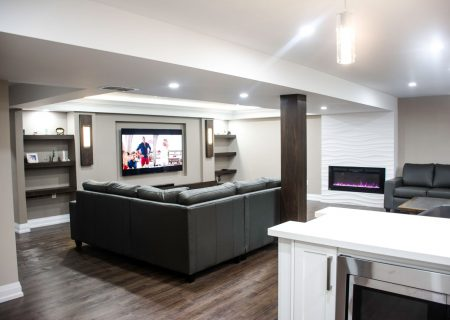 Luxury basement living room with black sofa and custom fire place