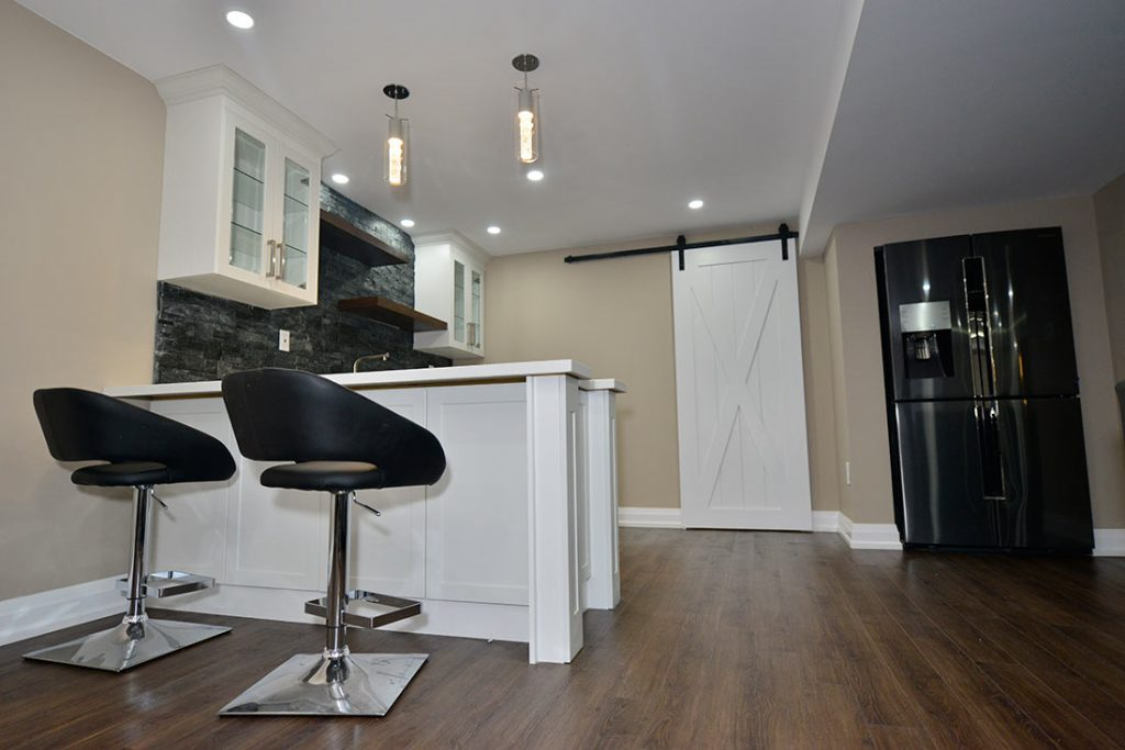 Custom kitchen with bar chairs in basement