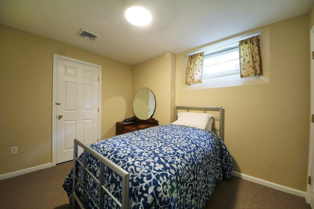 small bedroom with beige wall painting by harmony basements contractors toronto